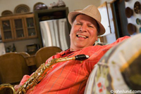 Picture of a happy smiling man sitting on a sofa at home with his saxophone. The man is laughing, jovial, and he is wearing fedora hat and a bright orange shirt on. This happy musician is looking at the camera.